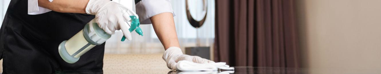 un agent de menage nettoie un support avec un produit d entretien