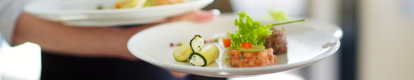 un serveur apporte deux plats aux clients dans un restaurant